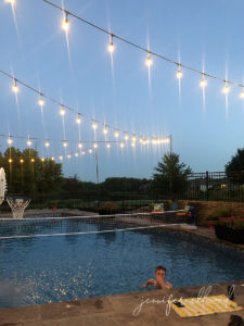 teen boy swimming in pool at dusk with string lights hung up over pool