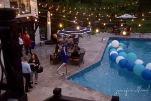 men and women gathered around pool at dusk with string lights hanging over the pool