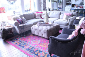 living room with off white couch, colorful decorations, and fuschia rug