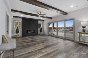 Bright and Light Basement Remodel with Black Fireplace and Large Windows