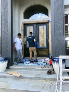 two contractors helping spray the front door gold