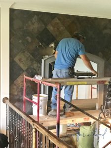 contractor man removing slate from wall