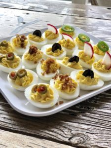 deviled eggs garnished with bacon bits, green olives, black olives, radishes, and jalepenos